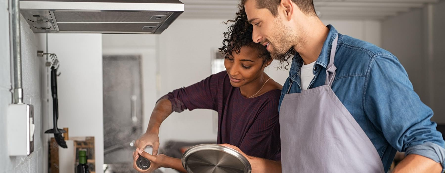 young couple cook over kitchen stove