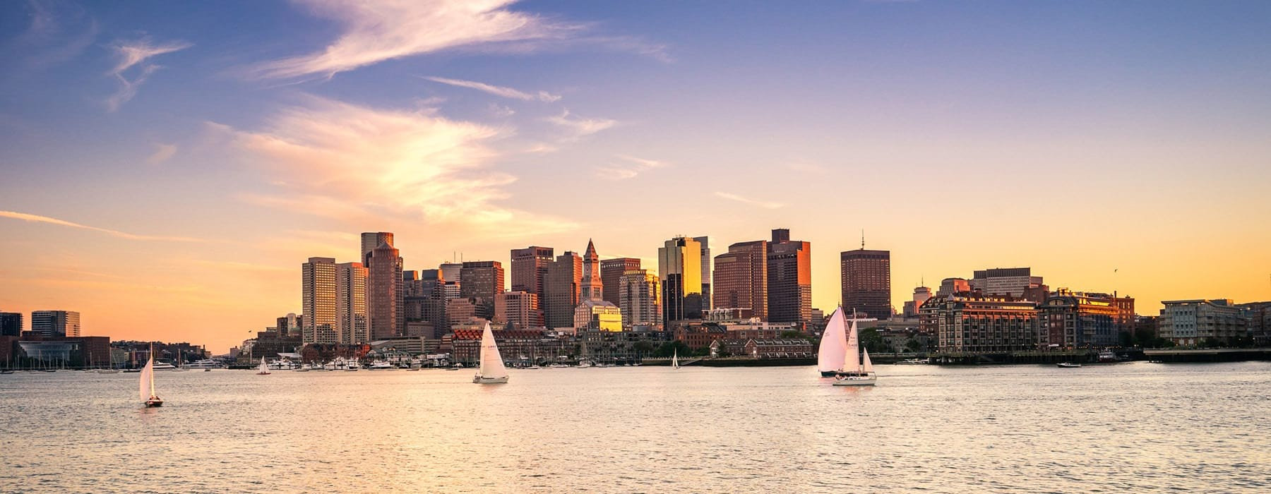 sailboats on the water with city skyline in the background